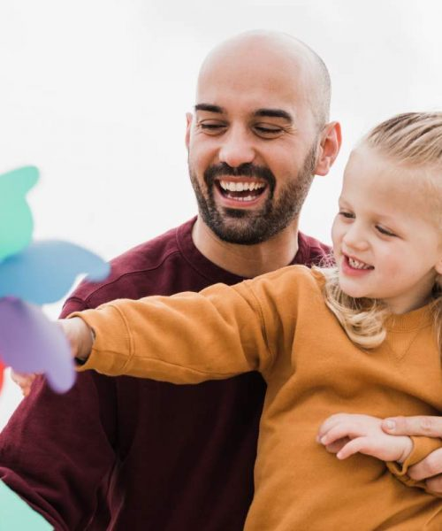 father-and-little-son-having-fun-with-pinwheel-toy-8QPU4TX